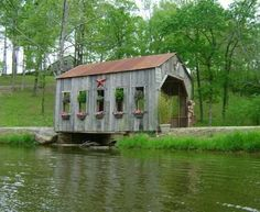 Moore Covered Bridge  Length = 85'  Built: March 2008 out of material salvaged from a very old barn. it was built by my husband Chad Moore and his brother Brad Vik. It took 2 days to complete. It is covering the spillway of our 8 acre pond.  Truss: Stringer  Photos by Leanne Moore (Owner)  Location:  927 Highway 70 E, Glenwood,. Three miles east of Glenwood on Highway 70.  Montgomery Co - AR