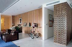 Living: uma das paredes foi revestida de freijó e recebeu uma prateleira de metal (4 x 0,50 m) para apoiar livros e objetos. O muxarabi, executado pela Laude Marcenaria, esconde a porta do lavabo (Foto: Lufe Gomes)