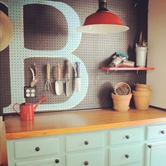 Painted peg board- seriously LOVING that huge monogram!! Craft room, laundry room, mud room.