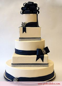 Navy Bow - This 5 tier round and square cake is covered in ivory fondant and decorated with navy bows and adorned with crystals. The entire cake was dark blue velvet cake with lemon cream cheese.