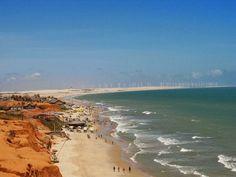 A praia e ao fundo as torres eólicas.