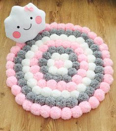 Handmade Cute and fluffy round Pom Pom rug consisting of three different colours (soft pink,light grey and white  Measures 80cm diameter This rug will look lovely in any room and is especially perfect for nurserys due to its soft and fluffy thickness ..... (Can also be made in other colours) Pom poms made will acrylic wool Rug grip backing Spot clean only