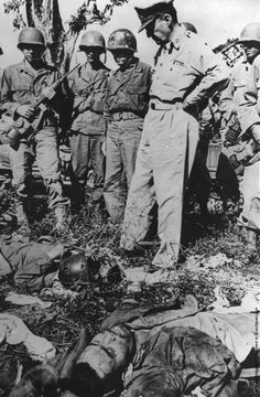 General Douglas MacArthur (1880–1964) looks down on dead Japanese soldiers after a fierce battle on Bataan. (Photo by Aaron/Hulton Archive/Getty Images). March 1945