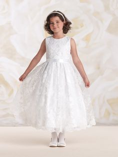 Sleeveless satin and lace tea-length A-line dress with jewel neckline, satin bodice with re-embroidered lace flower motif, removable double faced satin ribbon waistband, covered buttons down back, full gathered satin skirt features matching re-embroidered lace overlay and scalloped hem, perfect for as flower girl dress or as a First Communion dress. Sizes: 2 – 14
