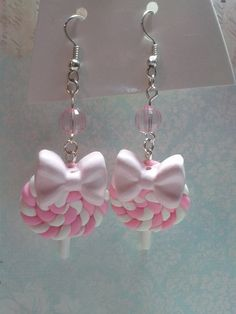 These adorable earrings are handmade by me. They feature pink and white swirled lollipops topped with pink bows as wells as pink beads.