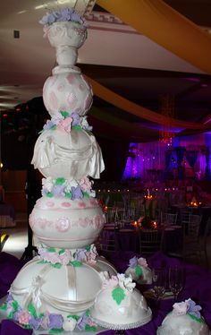 5 layer rounded wedding cake with goblet top, draping and vicotrian accents airbrushed in pink shimmer dust with purple and pink sugar flowers and satellite dome cakes.