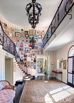A glorious tornado of photos, paintings, and even a bottle opener or two swirls down walls of the grand entry hall stairway in this stately home. - Photo: Tim Street-Porter / Design: Louise Voyazis