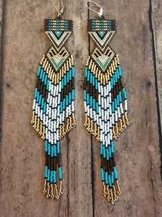 Name: Shape Shifters Beaded Earrings Size: 7 inches long ( with hooks 1 inch wide Colors: Turquoise blue, white, black, gold, bronze/brown These earrings are my original design and hand woven by me; they are truly one-of-a-kind. I have put many hours of work not only in the beading of them, but the designing as well. I have been beading for 20 years and I hope my experience shows through my work. For me, this is soul satisfying work and I hope my creations carry within it the energy an...