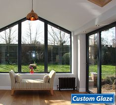 The light streams into this room through the church like gable window and the bi-fold doors. The customer chose to use dark grey aluminium frames. Using aluminium allows us to make the frames thinner than uPVC. Garage Extension, House Extension Design, Extension Designs, Extension Ideas, House Design, Grey Window Frames, Grey Windows, Front Doors With Windows, Conservatory Extension