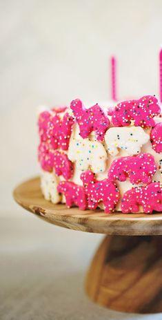 Iced sprinkle animal cookies pressed around the cake - so cute!