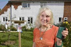 Stefanie Russell with the device that detects wireless signals and in the background, a workman painting the house