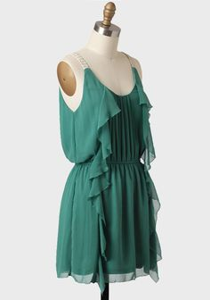 Adorned with shimmery cream-hued woven straps, this dark green dress features ruffled detailing and a flattering V-cut neckline. Finished with an elastic waistband for a defined silhouette, this fully-lined dress is the ideal option for any spring or summer semi-formal event.
