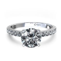 This striking platinum engagement ring features 20 pave set round brilliant diamonds totaling 1/5 carat and showcases the round center stone of your choice in a unique scalloped bottom four prong setting.