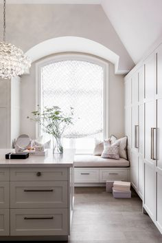 Chic walk-in closet features a high ceiling over a window seat alcove with barrel ceiling filled with a pink window seat under an arched window dressed in a white and gray roman shade. Beautiful closet boasts a crystal chandelier over a closet island facing a full wall of wardrobe cabinets. Designed by Elizabeth Metcalfe Interior Design