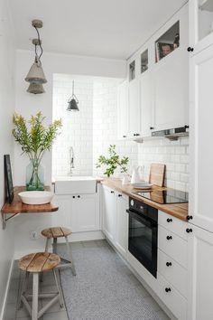 mała kuchnia | białe fronty kuchenne + drewniany blat + czarne gałki