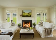 French doors flanking simple fireplace..love transoms