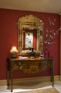 Love the table and this ornate mirror is exquisite. Notice how the artwork reflects in the mirror; good idea to place artwork across from mirror to create an enticing visual:)