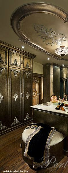 A LUXURIOUS SUMPTUOUS WALKIN CLOSET AND DRESSING ROOM FIT FOR ROYALTY.THE VERY LARGE MASTER CLOSET W/ENOUGH ROOM FOR ORNATE EMBELLISHED BUILT-INS FOR CLOTHES,SHOES,PURSES ETC.THE ORNATE EMBELLISHMENTS ,CARVED DESIGNS,CROWN MOULDING AND LUXURIOUS GOLD PAINTED BUILT INS GO PERFECTLY W/ARCHITECTURAL FEATURES AND DESIGN OF THE CEILING AND LARGE ISLAND AND CRYSTAL CHANDLIER AND STILL HAS PLENTY OF ROOM FOR DRESSING AND COULD ACCOMIDATE A SEATING AREA.I WOULD HANG A MORE LUXURIOUS…