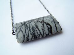 "Going solo, this necklace is all about modern simplicity and begins with 18 inches of antiqued gunmetal chain and a gorgeous slab of picasso jasper semiprecious stone in shades of black and gray. The stone is 1.4"" long x 1"" wide and is marbled with s   CLICK on the pic for more details.  http://www.multicolorgems.com"