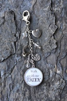 This beautiful bridal bouquet photo charm is double sided and designed in a silver finish, with a heart DAD charm, engagement ring, clear swarovski crystal beads , I Love You heart charm, Swarovski crystal beaded angel, and a heart clasp. Double sided pendant frame holds a photo on one side, and the words Walk With Me DADDY on other side ( wording is in a medium gray color with a white background). Designed for a bride who has lost her dad, this is a beautiful way for the bride to walk with…