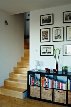 Staircase leading to hallway with books, plants and pictures displayed on top of a black storage table and pictures on the wall