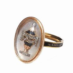 Fine quality high carat gold mourning ring dated 1780. The band supports a compartment set with a black enamel and rose-cut diamond urn on a mother of pearl ground and under crystal. The ring is described with the details of the deceased in gold letters on an enamel ground around the outer hoop :  Marg. Smith  Obt 30 Mar 1780 Ae 71.