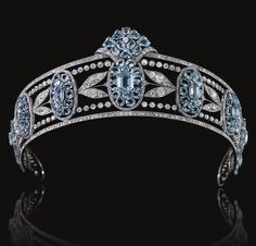 BELLE EPOQUE AQUAMARINE AND DIAMOND TIARA, CIRCA 1910. Designed as a series of graduated oval aquamarine clusters set with oval- and hexagonal-shaped aquamarines, interspersed with sprays of diamond myrtle leaves, within millegrain borders of circular-, single- and rose-cut diamonds, inner circumference approximately 370mm, fitted red leather and gilt tooled case.