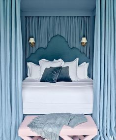 Fabulous blue bedroom features a blue Moorish style headboard on bed dressed in white and blue hotel bedding illuminated by polished nickel star wall sconces, Hudson Valley Lighting Barton Wall Sconce, surrounded by a blue canopy accented with blue silk curtains as well as a pair of pink x stools placed at the foot of the bed.