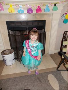 Birthday Princess wearing her sash in front of the fireplace decorations. Name banner I designed and put together, with 2 chandeliers on either side!