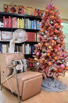 Rose gold colored Christmas tree with beauty parlor chair and bookshelves.