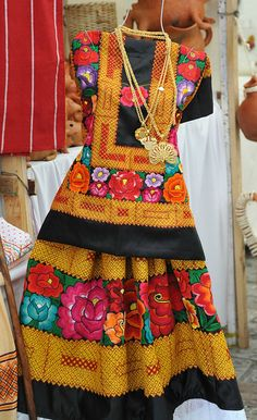 This huipil and long skirt are decorated by embroidered designs. The flowers are hand embroidered. The red and yellow designs were sewn using a machine. This traje is typical of the Isthmus of Tehuantepec region of Oaxaca, Mexico Mexican Costume, Mexican Outfit, Mexican Dresses, Mexican Style, Folk Costume, Mexican Clothing, Mexican Fashion, Ethnic Fashion, Mexican Textiles