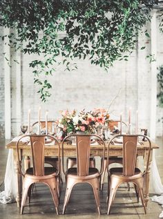 Wedding tablescape with bronze chairs, greenery above, and one large floral center piece