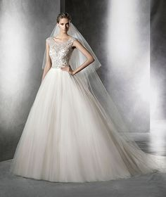 Princess wedding dress in tulle with gemstones. Bodice with bateau neckline and sheer underbodice with sweetheart neckline. Wide skirt in plain tulle.