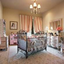 "This baby girl's nursery was designed to ""grow with her"". The iron crib can be converted to a daybed, and the hand-painted dresser has timeless appeal."