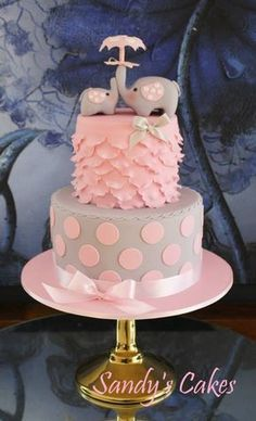 This pink and gray elephant baby shower cake has great detailing, like satin ribbon, polka dots, and ruffles, topped with a sweet mother and baby elephant! This cake will be sure to grab everyone's attention at your party! Torta Baby Shower, Tortas Baby Shower Niña, Unique Baby Shower Cakes, Elephant Baby Shower Cake, Elephant Cakes, Elephant Theme, Pink Elephant, Bolo Laura, Baby Girl Cakes