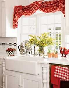 Apple red curtains, along with coordinating collectibles and dish towels, add a splash of color to this pristine white kitchen.