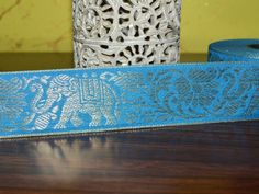 Beautiful Blue Color Jacquard ribbon border trim with Elephant Pattern. Trim is decorated with silver color metallic thread embroidery.   This stunning lace can be used for designing stylish...