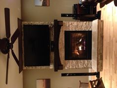 Stone on fireplace with tv mounted over mantle. I like the mantel but do not like the fake stone