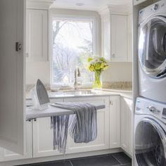Stacked washer/dryer with drop down ironing board