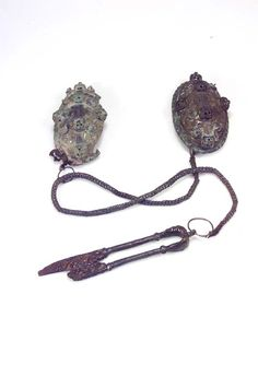 "Oval brooches with snips hanging from Viking ""knitted"" chain. Note how the chain is attached to one brooch, but passes through a wire ring attached to the second brooch."