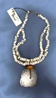 Rita Okrent | Antique Tibetan shell beads and pendant, and small beads of antique amber from Morocco, and brass heishi from Africa