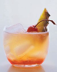 Chinatown Sling (Makes 8) (16 ounces pineapple juice   10 ounces gin   4 ounces triple sec   4 ounces Bénédictine   1 scant teaspoon Angostura bitters   Ice   2 ounces cherry liqueur, preferably Cherry Heering   8 pineapple spears   8 maraschino cherries)