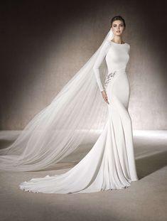 MANON  Vestido de novia de corte sirena en crepe con manga larga y escote caja que realza la figura gracias a su delicado detalle de pedrería en la cadera. Sofisticado
