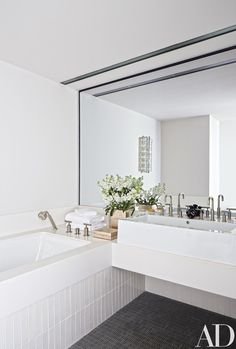 The master bath features a Kohler tub and fittings and a Lacava sink, as well as towels by Natori Home; the tile on the tub surround is by Nemo Tile Co., and the flooring is by Ann Sacks | archdigest.com