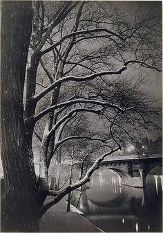 Brassaï - Les arbres des quais avec le Pont-Neuf - ca. 1945.   El Puente Nuevo que a pesar de su nombre, es el más antiguo de todos los puentes que cruzar el río Sena, es el primer puente construído en piedra en Paris. Es monuménto histórico. Y otra fotografía que invita a caminar el ella.