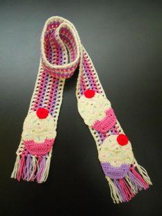 CACHECOL CUPCAKES: de crochê em lã 100% acrílica.  Aplicação de cupcakes de crochê nas extremidades. Detalhes de canutilhos bordados.  Comprimento: 120 cm. R$ 55,00.
