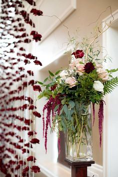 Glass vases of roses and amaranth flanked either side of the carnation backdrop ~ we ❤ this!moncheribridals.com