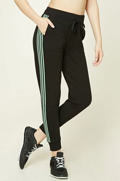 A pair of knit sweatpants featuring contrast striped side panels, ribbed trim, elasticized drawstring waist, two front slit pockets, fleece lining, and cuffed ankles.