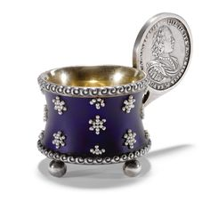 A Fabergé silver, enamel and seed pearl charka, Moscow, 1908-1917, circular, the waisted sides with translucent royal blue matte enamel set with seed pearl stars, Slavic scroll borders, ball feet, gilt interior, the handle inset with a silver coin depicting Peter the Great.
