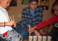 Part of an all-school, all-age, activity group celebrating the Chinese New Year with a game where chopsticks are used to pick up a ping-pong ball.